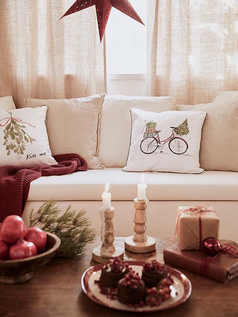 Przytulny salon z jasną sofą i czerownymi poduszkami udekorowany n święta