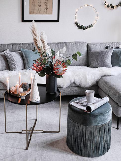 Salon z szarą sofą i czarnym stolikiem kawowym udekorowany stroikiem bożonarodzeniowym i kwiatami