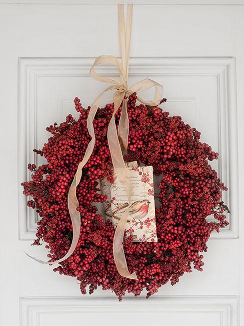 Wieniec świąteczny z głogu z jasną wstążką na białych drzwiach