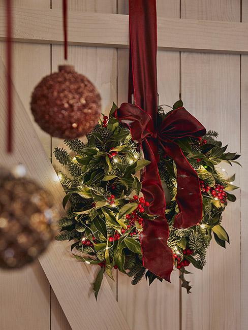 Wieniec bożonarodzeniowy z liści ostrokrzewu na drzwiach wejściowych z