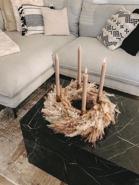 Stroik bożonarodzeniowy na stole z marmuru zrobiony z suszonych traw i świeczek