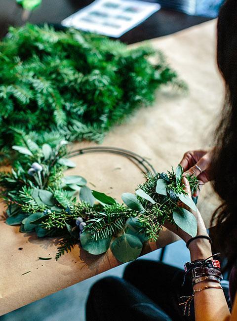 kobieta robiąca wieniec z liści eukaliptusa i świerku