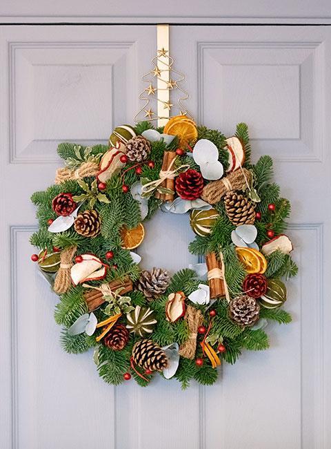 Wieniec adwentowy z liści świerku, pomarańcz, lasek cynamonu i szyszek na drzwiach wejściowych