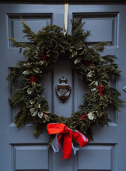 Wieniec adwentowy z liści świerku na drzwiach wejściowych