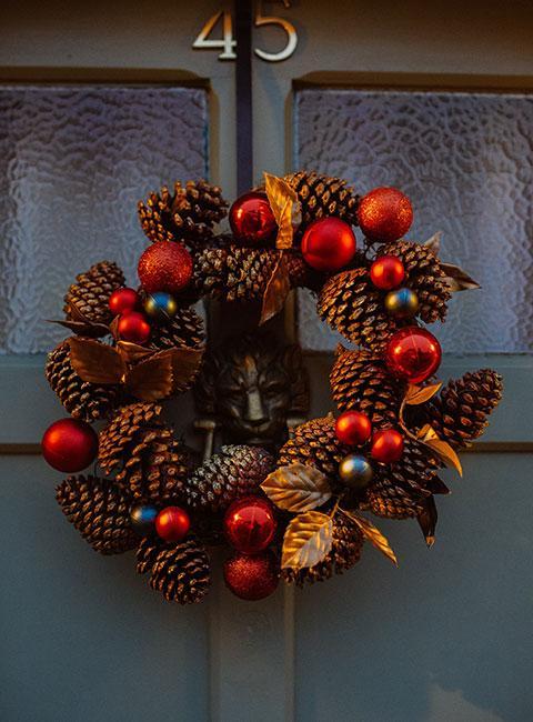 Wieniec świąteczny z szyszek i czerwonych bombek na ciemnych drzwiach