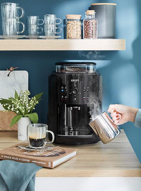 Nowoczesny czarny exspres do kawa w kuchni z niebieską ścianą