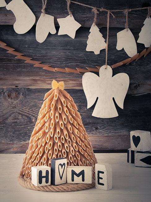 Choinka z makaronu na białym stoliku na tle drewnianej ściany z białą girlandą