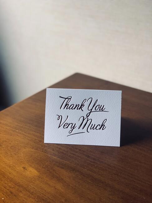 życzenia na dzień chłopaka: Biała kartka z podziękowaniami na drewnianym stole