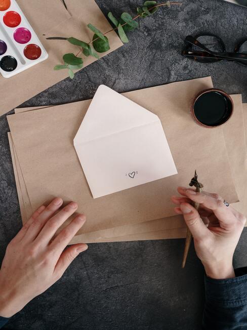 Dłonie na biurku trzymające długopis w ręku, przed nimi koperta