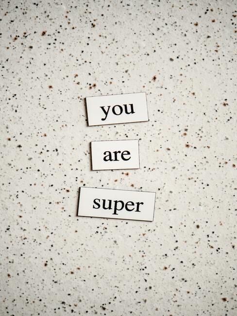 """napis """"jestes super"""" na marmurowym blacie"""