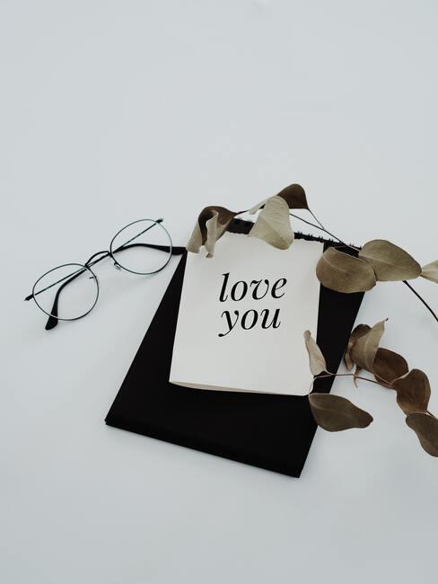 """biała kartka z napisem z czarną ramką """"Kocham Cie"""", obok okulary"""