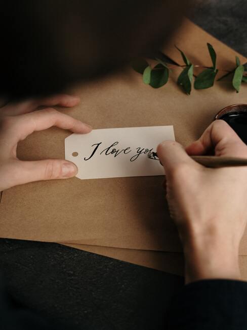 """Osoba pisząca na małym skrawku papieru """"kocham Cie"""""""