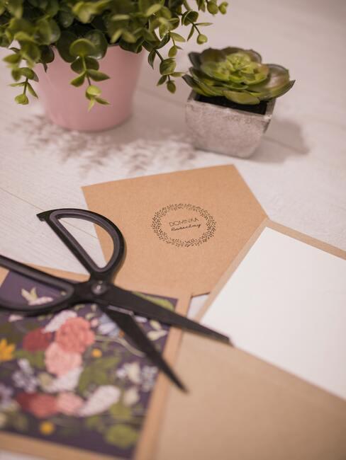 Kartka z życzeniami na stole, obok kwiatek i nożyczki