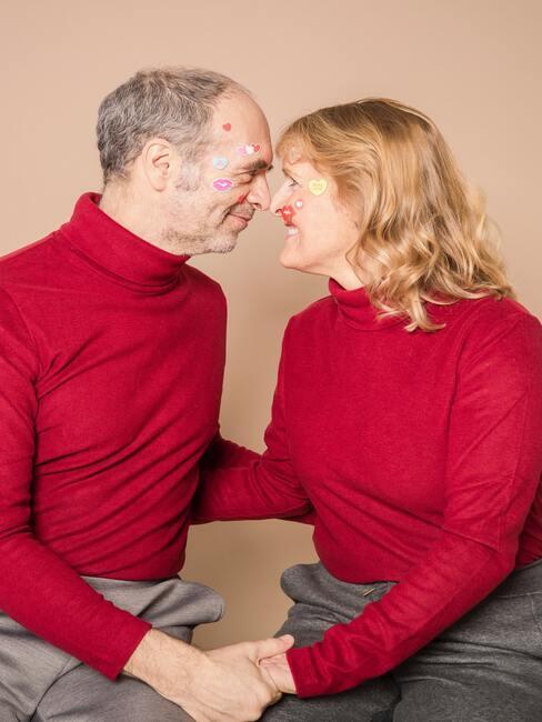 Para straszych ludzi w czerwonych swetrach przytulająca się czołem