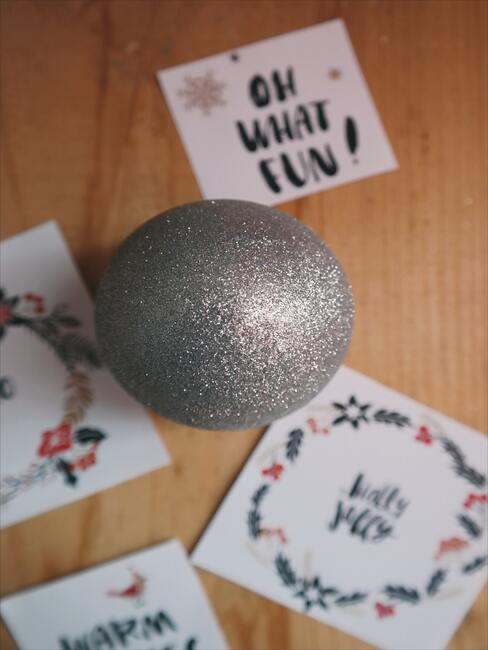 życzenia mikołajkowe: Porozrzucane świąteczne kartki na stole i bombka choinkowa