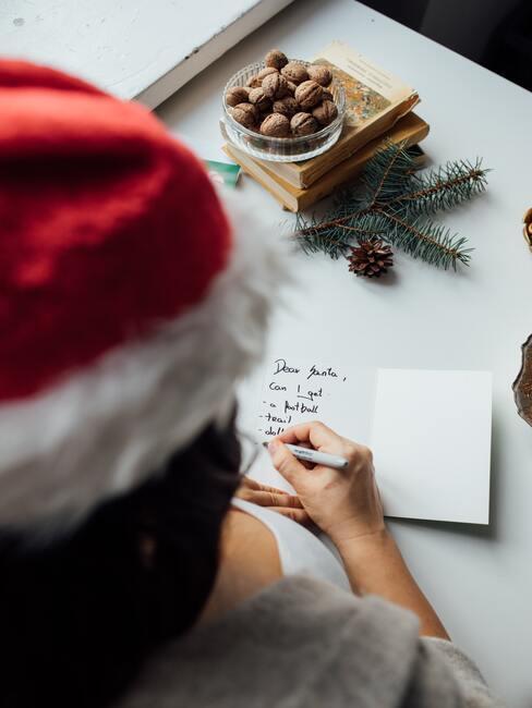 Osoba w czapce Mikołaja pisząca kartkę do Mikołaja