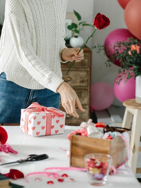 życzenia mikołajkowe: Osoba w białym swetrze pakująca prezenty