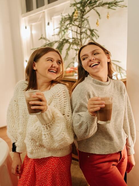 życzenia mikołajkowe: Dwie dziewczyny ubrane w takie same ubrania stojąca przed choinką, śmiejące się i pijące kawę w szklance
