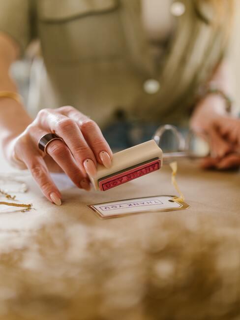 Osoba odciskająca pieczątkę ma kartce z życzeniami