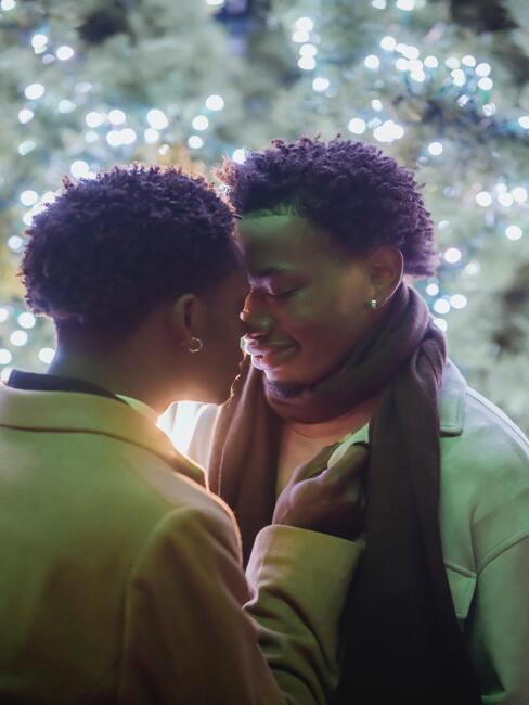 Para przytulająca się przed choinką