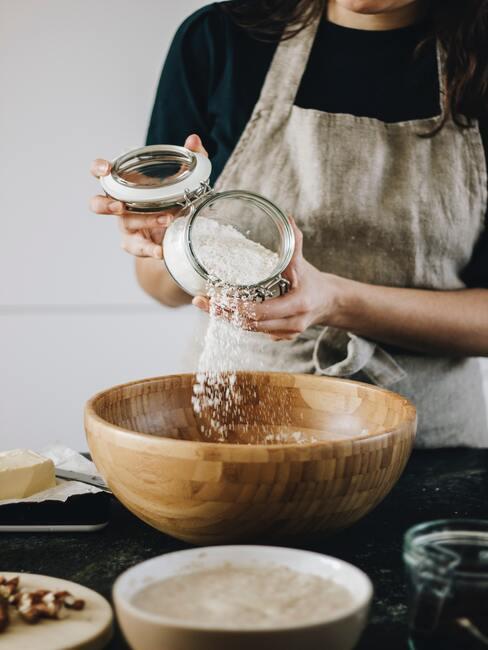 Osoba w fartuchu kuchennym wsypująca mąkę do drewnianej miski