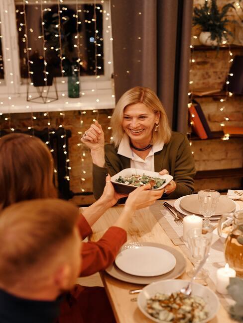 dzielenie się opłatkiem: Rodzina przy wigilijnym stole zastawionym przeróżnymi potrawami