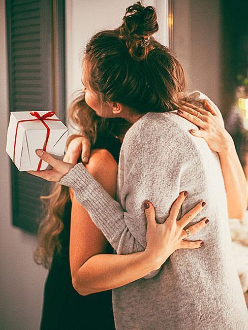 dzielenie się opłatkiem: Dwie osoby przytulające sie i dające sobie prezenty