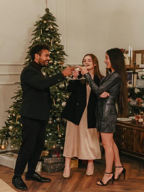 dzielenie się opłatkiem: trzy osoby odświętnie ubrane wznoszące toast przy choince