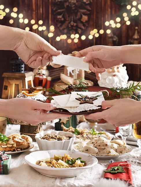 Zbliżenie na dłonie dzielące się opłatkiem na tle stołu wigilijnego