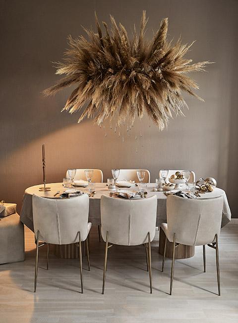 Stół w beżowych kolorach przygotowany na odświętną kolację z dekoracją z trawy pampasowej zawieszoną nad stołem