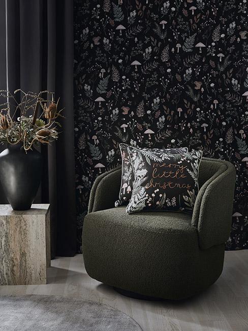 zielony fotel z poduszkami świątecznymi na tle czarnej fototapety w drobne kwiatki