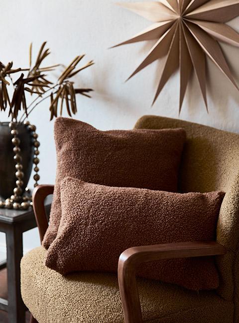 Zbliżenie na brązowe poduszki z boucle na beżowym fotelu w salonie z dekoracjami świątecznymi w kolorach ziemi