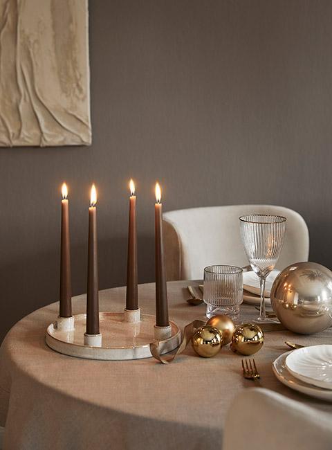 cztery brązowe świece na stole wigilijnym ze złotymi bombkami