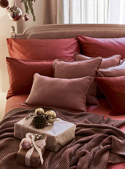 Zbliżenie na łóżko z poduszkami w kolorach bórówek z prezentami na narzucie