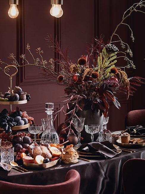 zbliżenie na ciemny barokowy stół w odcieniach purpury z obfitością jedzenia i wazon z kwiatami
