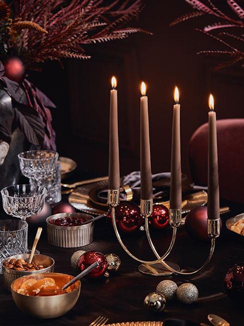 zbliżenie na świecznik z brązowymi świeczkami na tle ciemnej jadalni w kolorach purpuru