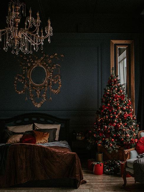 Ciemna wiktoriańska sypialnia z okazałym żyrandolem i choinką z tradycyjnymi dekoracjami z welwetu