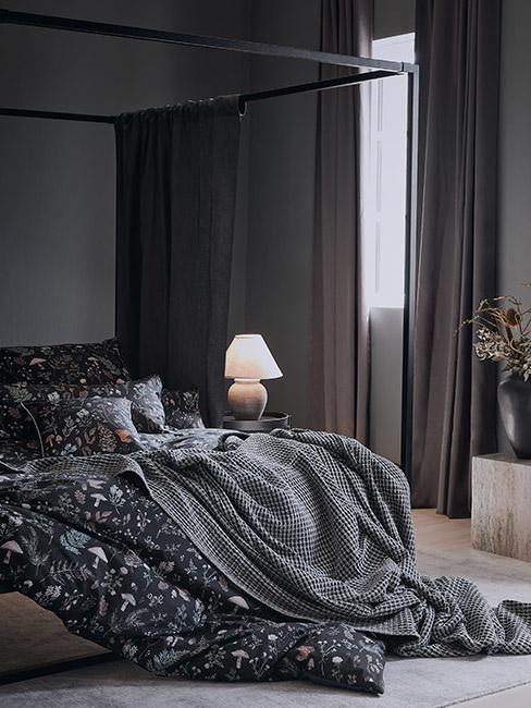 Ciemna sypialnia z czarną pościelą w świąteczne wzory kwiatowe