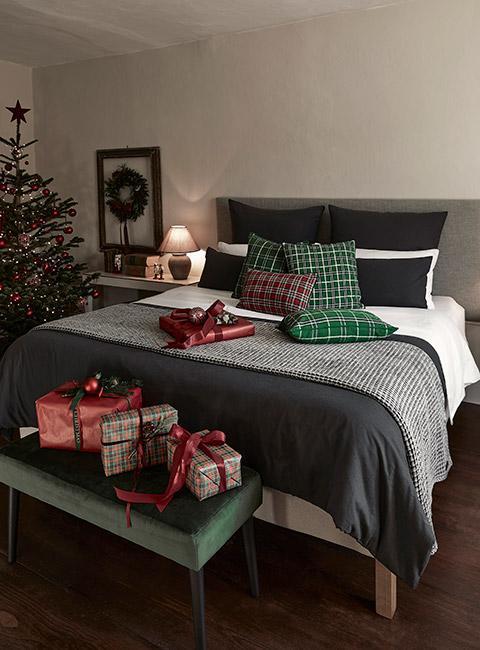 Sypialnia udekorowana świąteczne z poduszkami w kratkę i prezentami w kratkę