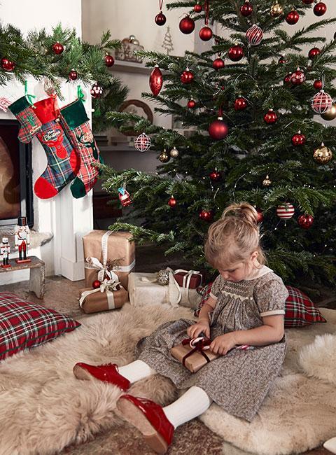 Dziewczynka siedząca na owczej skórze przy świątecznym kominku obok choinki