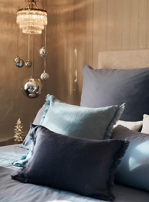 Zbliżenie na poduszki na łóżku w odcieniach niebieskiego z bombkami w na żyrandolu w tle
