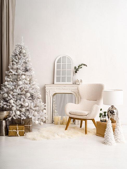 Biała choinka z białymi dekoracjami w salonie z fotelem z tkaniny boucle i kominkiem