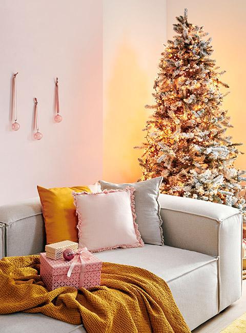 Pastelowy salon z beżową sofą i poduszkami w różu i żółci z pastelową choinką w tle