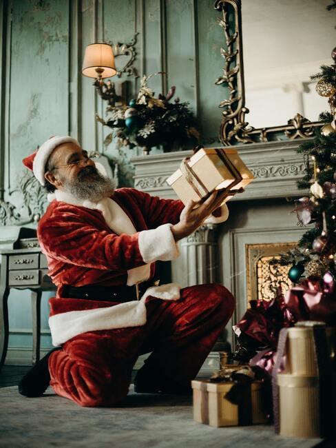 Mikołaj obok choinki oglądający prezenty