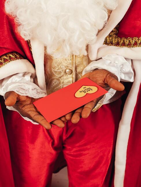 jak napisać list do świętego mikołaja: Święty Mikołaj trzymający list w czerwonej kopercie