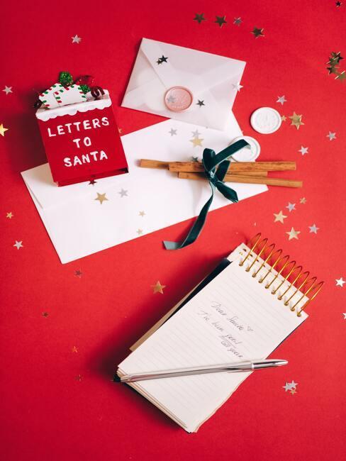 jak napisać list do świętego mikołaja: białe kartki papieru na których będzie pisany list do Mikołaja, na czerwonym tle