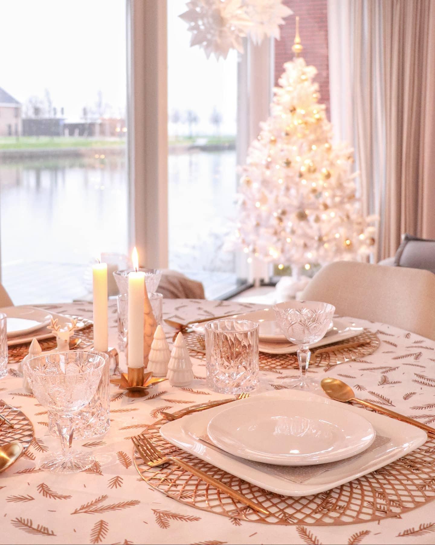 JAsna jadalnia z wigilijnym stołem z białą cjoinką w tle
