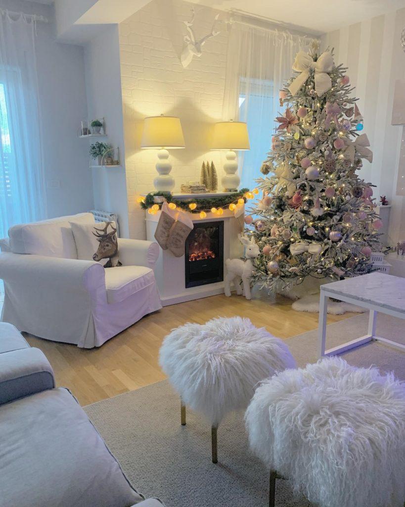 biały salon z kominkiem z choinką z różowymi i złotymi dekoracjami