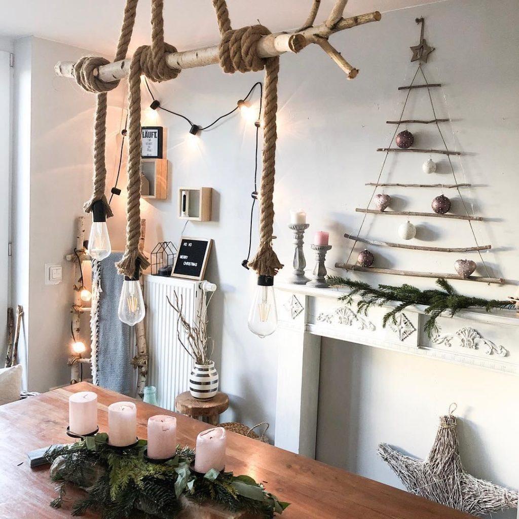 Jadalnia w stylu industrialnym z wiszącą lampą z żarówkami i choinką z patyków na ścianie