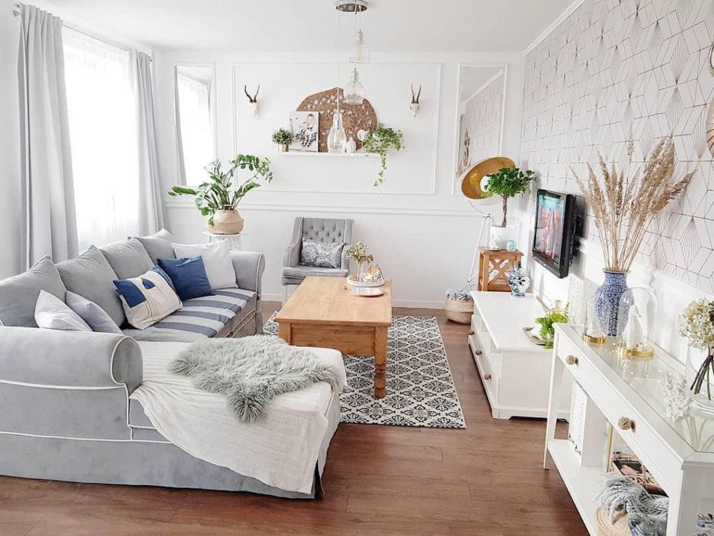 Mały salon w stylu hampton z szarą sofą, niebieskimi poduszkami i białymi meblami